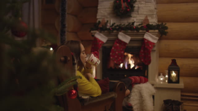 Woman relaxing by the fire in a chalet Woman relaxing in an armchair by the fire christmas stocking stock videos & royalty-free footage
