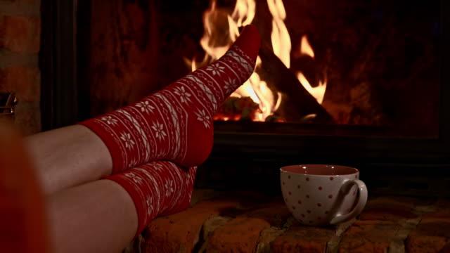 stockvideo's en b-roll-footage met ds vrouw ontspannen bij de open haard - christmas cabin