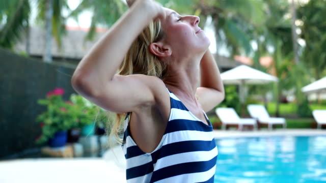vídeos y material grabado en eventos de stock de mujer relajante junto a la piscina, brazos estirados - miembro humano