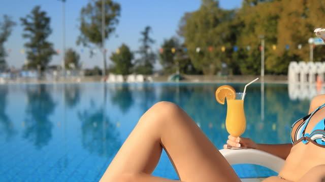 hd dolly: frau entspannung am swimmingpool - sun chair stock-videos und b-roll-filmmaterial