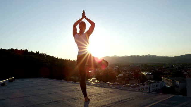 CLOSE UP: Woman relaxing doing tree pose on the top of skyscraper at sunset video