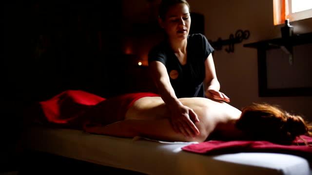 woman relaxing during massage at the spa - terapia lastone filmów i materiałów b-roll
