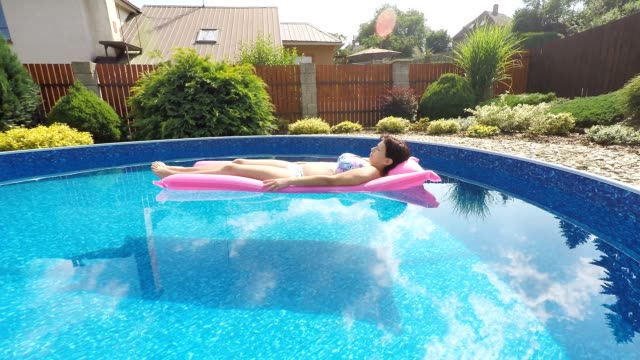 Woman relaxing in a small home swimming pool video