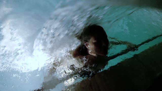 frau entspannen in einem beleuchteten hydromassage-pool mit fallendem wasser in der nacht - sauna und nassmassage stock-videos und b-roll-filmmaterial