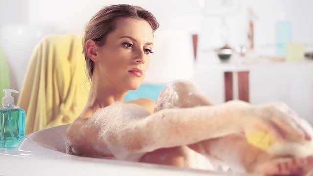 女ソープ スポンジで足を泡洗浄彼女とバスタブでリラックス - 体 洗う点の映像素材/bロール