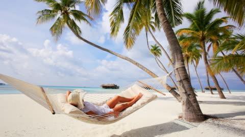 donna rilassante in un'amaca sulla spiaggia. - idillio video stock e b–roll