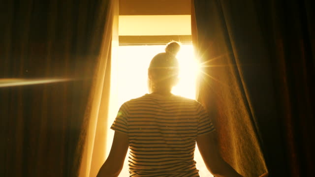 Woman relaxing in front of the window. Woman relaxing in front of the window in a beautiful sunny day. dawn stock videos & royalty-free footage