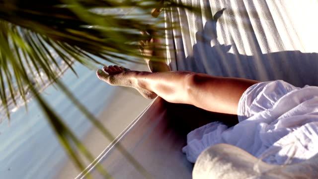 stockvideo's en b-roll-footage met woman relaxing in hammock under palm tree - zwart haar