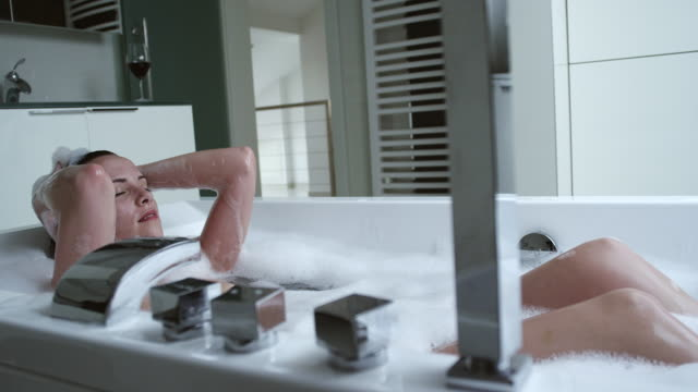 Woman relaxing in modern bathtub – Video