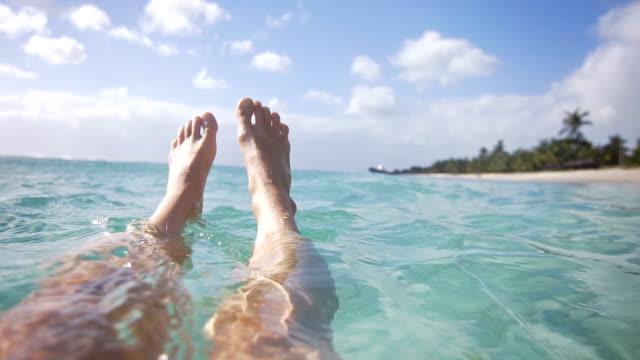vídeos de stock, filmes e b-roll de mulher relaxante no oceano com os pés flutuando na água - flutuando na água