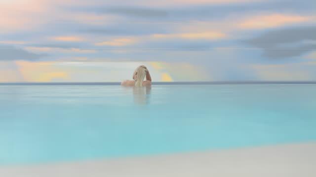 vídeos de stock, filmes e b-roll de slo mo ws mulher relaxando na piscina - azul turquesa