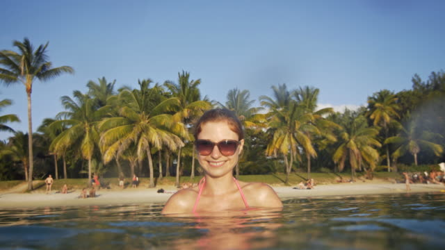 Woman relaxing in the ocean and splashing into the camera video