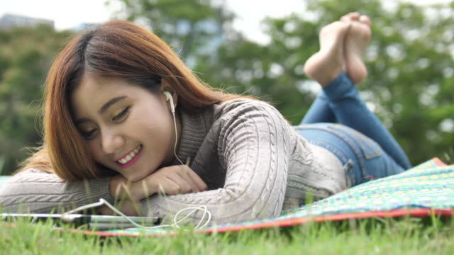 SLO MO Woman relaxing listening music in Park video