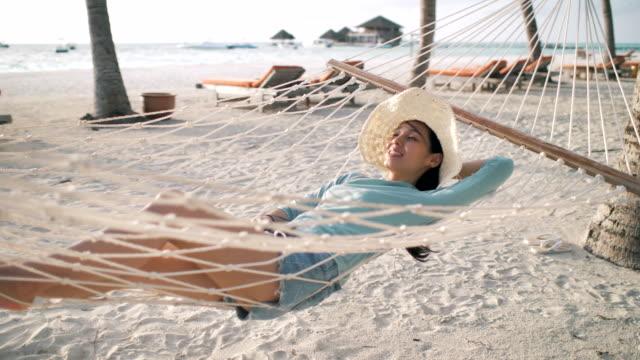 stockvideo's en b-roll-footage met vrouw die liggend op hangmat op strand ontspant - caraïbische zee
