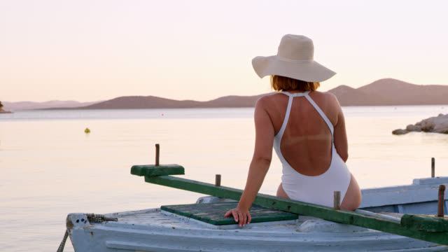 DS Woman relaxing on a boat at sunset Dolly shot of an unrecognizable mid-adult woman relaxing on an old wooden boat in the bay at sunset. Shoot in 8K resolution. swimwear stock videos & royalty-free footage