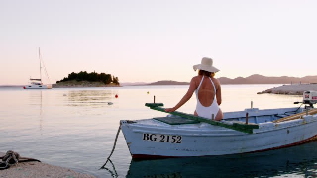 DS Woman relaxing on a boat at sunset video