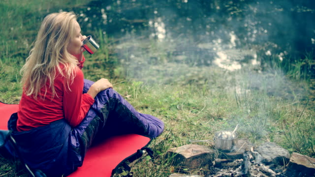 Woman relaxing on a lake shore. Drinking hot beverage - video
