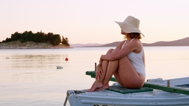 LS Woman relaxing on an old wooden boat at sunset video