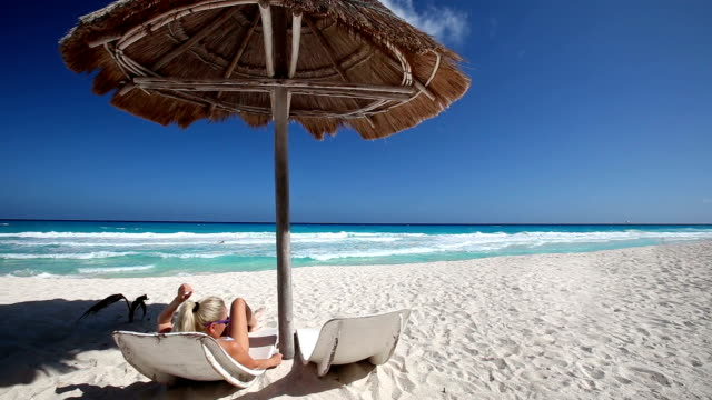 Woman relaxing  on caribbean beach with sun umbrella and wooden bed video
