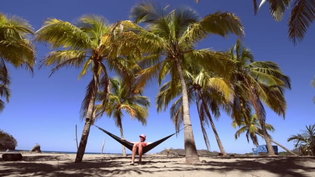 Woman relaxing on hammock under palm trees in Costa Rica video