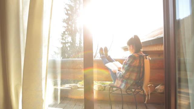 kobieta relaks na balkon kabiny i czyta książkę. - kabina filmów i materiałów b-roll