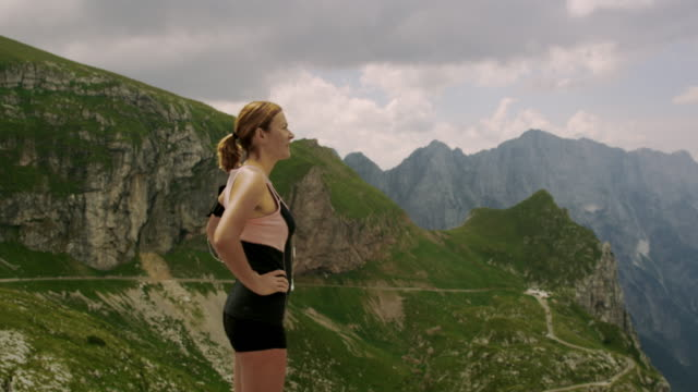 SLO MO Woman relaxing on the top of a mountain Slow motion shot a woman relaxing on the top of a mountain ridge. Mangart or Mangrt is a mountain in the Julian Alps. Slovenia. mid adult women stock videos & royalty-free footage