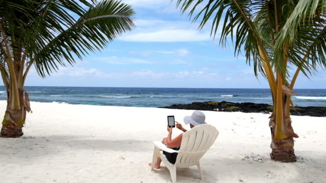 Woman relaxing on vacation sitting on tropical beach under palm trees on deckchair reading an electronic book or e-reader video