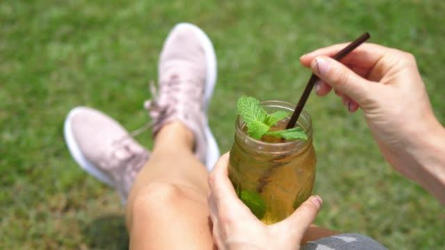 vídeos de stock, filmes e b-roll de mulher que relaxa ao ar livre com chá gelado fresco da hortelã no verão - tea drinks
