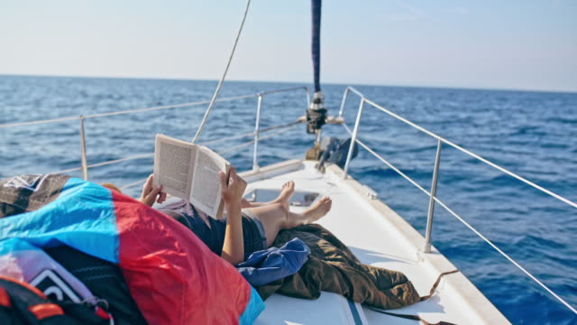 4K Woman relaxing, reading book on sunny sailboat, real time
