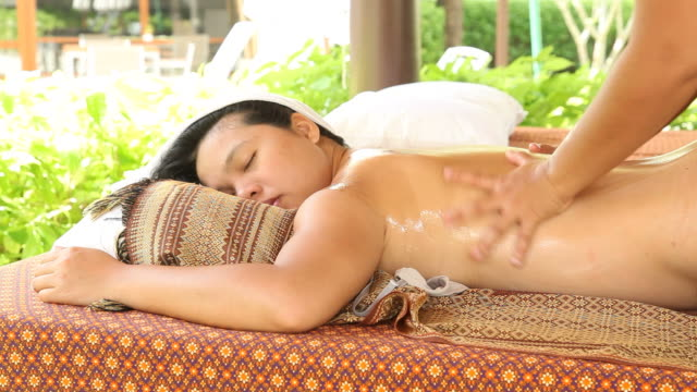 stockvideo's en b-roll-footage met woman relaxing while getting body oil massage - massagetherapeut
