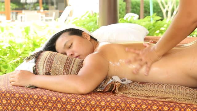 woman relaxing while getting body oil massage - massageterapeut bildbanksvideor och videomaterial från bakom kulisserna