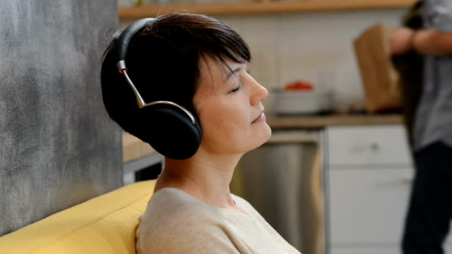 Woman Relaxing with Headphones Short haired caucasian woman 40, with headphones looking very relaxed and peaceful while someone walks behind her. zen like stock videos & royalty-free footage
