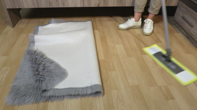 Woman remove rug and start cleaning by mop - vídeo