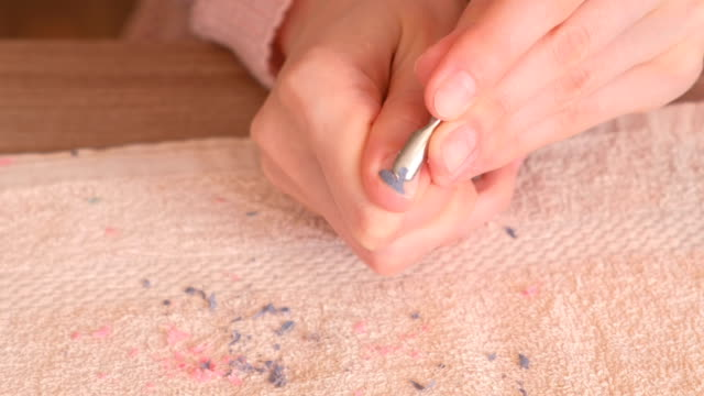 woman removes shellac from nail with pusher. close-up hand. - rimuovere video stock e b–roll