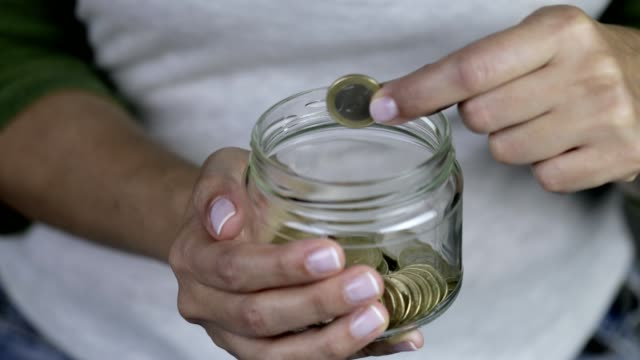 Woman removing one Euro coin from savings in Jar