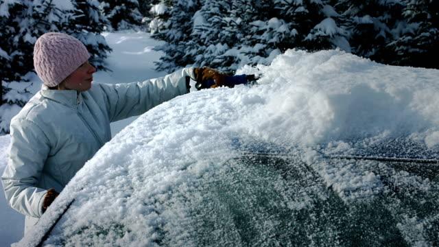 kvinna att ta bort snö från en blå bil - vindruta bildbanksvideor och videomaterial från bakom kulisserna
