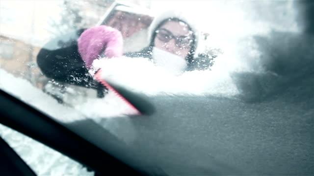 kvinna att ta bort snö från bilen vindruta - vindruta bildbanksvideor och videomaterial från bakom kulisserna