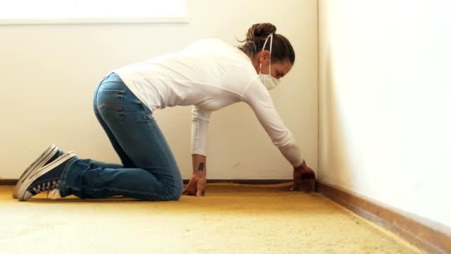 donna rinnovatrice strappa vecchio tappeto - moquette video stock e b–roll