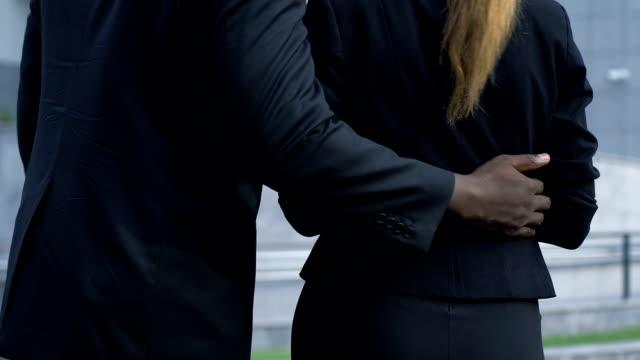 donna respinge collega maschio cercando di abbracciarla, molestie sessuali sul lavoro - violenza donne video stock e b–roll