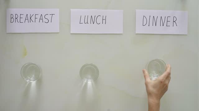 под названиями женщина заменяет тарелки завтраком, обедом и ужином стаканами с водой. интервальный пост концепции. пропуск приема пищи - поститься стоковые видео и кадры b-roll