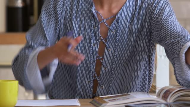 stockvideo's en b-roll-footage met vrouw onderzoeken en maken merkt op de keukentafel, close-up, geschoten op r3d - woman home magazine
