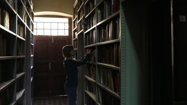 woman researching bookshelf - quarantenne video stock e b–roll