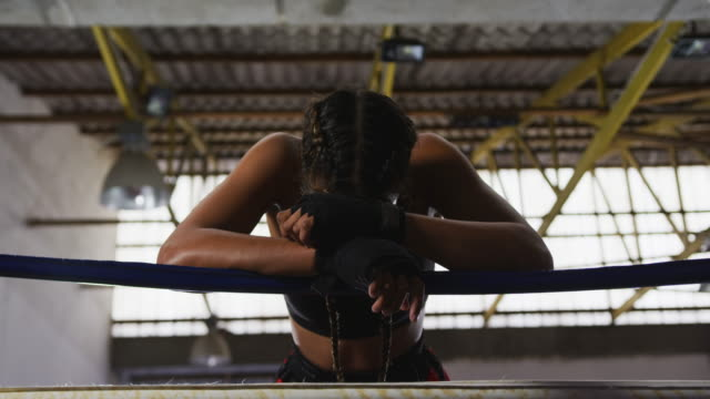 Woman resting after working out in voxing club Mixed race female boxer with plaited hair wearing a vest, boxing shorts and with hands wrapped, leaning on the ropes in a boxing ring at a boxing gym, resting after training, slow motion leaning stock videos & royalty-free footage
