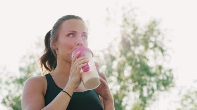 Kvinnan vilar och dricker en proteinshake efter hennes träning video