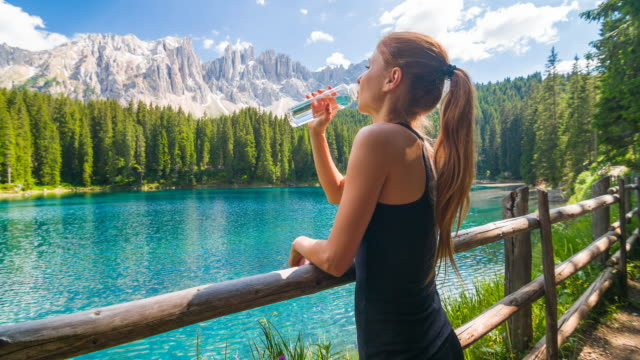 Woman resting at mountain lake, hydrating from a reusable water bottle Young woman standing by mountain lake, surrounded by mountains, hydrating, drinking water from a reusable water bottle and admiring the view on a beautiful sunny day saturated color stock videos & royalty-free footage