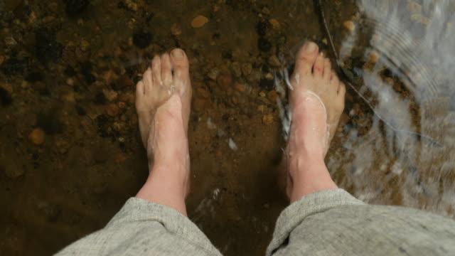 vídeos de stock e filmes b-roll de woman resting her feet in a cool mountain stream, river, or lake - mulher deixar ir