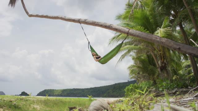 躺在棕櫚樹上的吊床上的女人 - 休閒器具 個影片檔及 b 捲影像