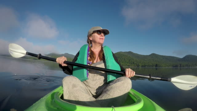 Woman resting in a kayak enjoying the view of the mountain lake