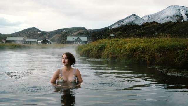 아이슬란드에서 뜨거운 천연 수영장에서 휴식 하는 여자 - 스파 온천 스톡 비디오 및 b-롤 화면