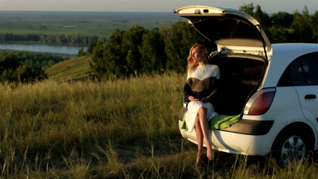 woman resting in the trunk of a car on a cliff